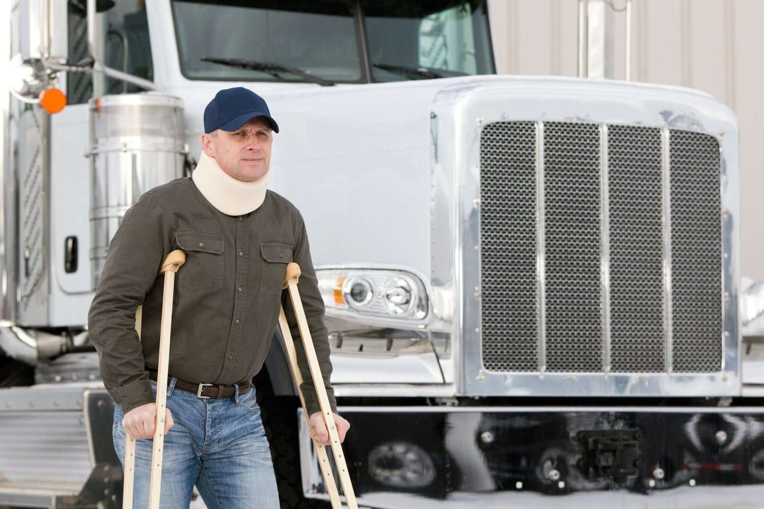A minor standing next to his truck on crutches with whiplash